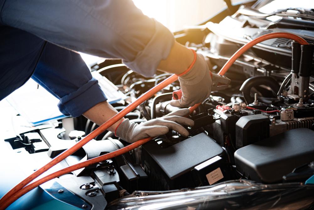Mecánico trata de cargar la batería de un coche